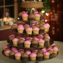 Five tiers of pink and chocolate cupcakes.