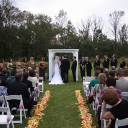 Bride and groom stand beneath a wedding pergola.