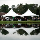 Two large wedding tents are reflected in a lake.
